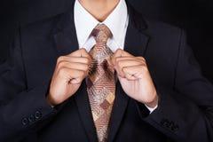 Nahaufnahme des Geschäftsmannes seine Halsbindung reparierend Stockfotografie