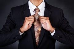Nahaufnahme des Geschäftsmannes seine Halsbindung reparierend Lizenzfreie Stockfotografie