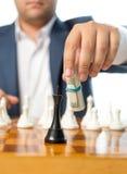 Nahaufnahme des Geschäftsmannes spielend mit verdrehten Dollar an Schach gam Stockbild