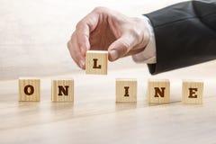 Nahaufnahme des Geschäftsmannhandzusammenbauenden Wortes ONLINE mit sechs Holz Lizenzfreie Stockfotografie
