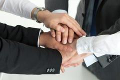 Nahaufnahme des Geschäftsteams Einheit mit dem Setzen ihrer Hände zeigend Lizenzfreie Stockfotos