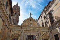 Nahaufnahme des geschnitzten Marmorportal- und Kirchenglocketurms mit Glühen von der Sonne in Venedig Lizenzfreies Stockfoto