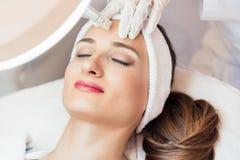 Nahaufnahme des Gesichtes einer Frau, die während der nicht-chirurgischen Gesichtsbehandlung sich entspannt Stockbilder