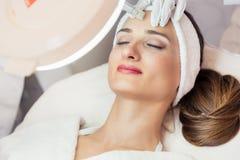 Nahaufnahme des Gesichtes einer Frau, die während des nicht-chirurgischen fac sich entspannt Stockfotos
