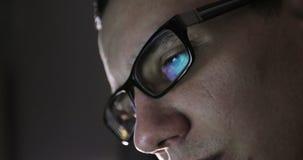 Nahaufnahme des Gesichtes eines jungen Mannes mit Gläsern in der Dunkelheit stock footage