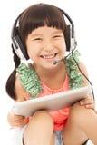 Nahaufnahme des glücklichen kleinen Studentenmädchens, das eine Tablette hält Lizenzfreie Stockfotos