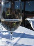 Nahaufnahme des Glases mit Weißwein- und Lichtreflexionen auf einem Gedeck draußen lizenzfreie stockfotos