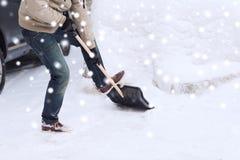 Nahaufnahme des grabenden Schnees des Mannes mit Schaufel nahe Auto Stockfoto