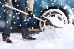 Nahaufnahme des grabenden Schnees des Mannes mit Schaufel nahe Auto Stockfotografie