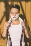 Nahaufnahme des gutaussehenden Mannes mit dem Rasieren des Schaums auf seinem Gesicht und Tuch stockfotografie