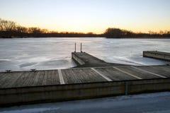Nahaufnahme des hölzernen Piers bei Sonnenuntergang in gefrorenem Eis bedeckte See stockbild