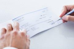 Nahaufnahme des Handfüllenden Schecks Stockbild