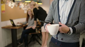 Nahaufnahme des Handjungen Mannes benutzt Tablette des Bildschirm- und trinkenden Kaffee im modernen Startbüro Lizenzfreies Stockbild