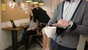Nahaufnahme des Handjungen Mannes benutzt Tablette des Bildschirm- und trinkenden Kaffee im modernen Startbüro Lizenzfreie Stockfotos