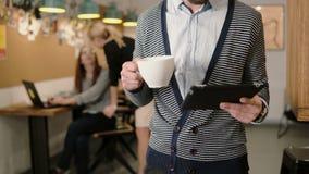 Nahaufnahme des Handjungen Mannes benutzt Tablette des Bildschirm- und trinkenden Kaffee im modernen Startbüro Lizenzfreie Stockfotografie
