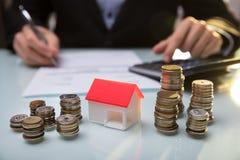 Nahaufnahme des Haus-Modells And Stacked Coins auf Schreibtisch lizenzfreies stockfoto