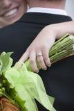 Nahaufnahme des Hochzeitsringes mit Braut und Bräutigam im Hintergrund Lizenzfreie Stockfotos