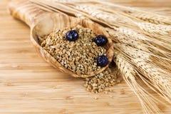 Natürliches ganzes Korn-Getreide im hölzernen Löffel Stockfotos