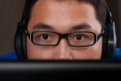 Nahaufnahme des jungen asiatischen Mannes, der auf Computer spielt Lizenzfreie Stockfotos