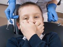 Nahaufnahme des Jungen bedeckt seinen Mund in Zahnarzt ` s Stuhl und betrachtet die Kamera Stockfoto