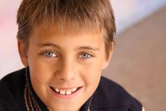 Nahaufnahme des Jungen lächelnd gegen bunten Hintergrund Lizenzfreies Stockfoto