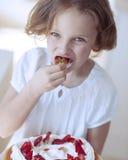 Nahaufnahme des jungen Mädchens mit Kuchen Erdbeere essend Stockfotografie