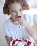 Nahaufnahme des jungen Mädchens mit Kuchen Erdbeere essend Lizenzfreie Stockfotografie