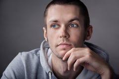Nahaufnahme des jungen Mannes auf grauem Hintergrund Stockfoto