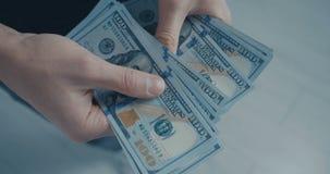 Nahaufnahme des jungen Mannes zählt die Dollaranmerkungen nach, die im Büro stehen Dollar in der Hand, Geld in der Hand, zählt da stock video footage