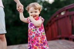 Nahaufnahme des kleinen Mädchens, die Dad& x27 hält; s-Hand auf Brücke Stockbild