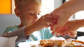Nahaufnahme des kleinen netten Jungen, der Pizza isst stock video footage