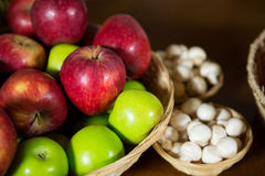 Nahaufnahme des kleinen Weidenkorbes voll der Äpfel am organischen Abschnitt Lizenzfreies Stockbild