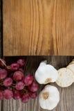 Nahaufnahme des Knoblauchs, der Trauben, des Crackerkekses und des hackenden Brettes Lizenzfreies Stockbild