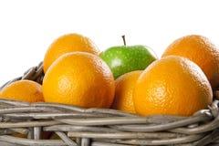 Nahaufnahme des Korbes der Orangen und des Apfels Stockbild