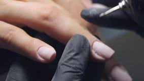 Nahaufnahme des Kosmetikerschleifens das Nagelstudio für eine Maniküre im Schönheitssalon stock video