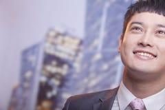 Nahaufnahme des lächelnden jungen Geschäftsmannes, der oben schaut Lizenzfreies Stockbild