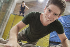Nahaufnahme des lächelnden jungen Mannes, der oben einen Kletterwand in einer kletternden Innenturnhalle klettert lizenzfreies stockfoto