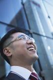Nahaufnahme des lächelnden und lachenden Geschäftsmannes, der oben mit Glasreflexion des Wolkenkratzers schaut Stockfoto