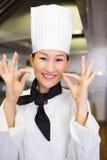 Nahaufnahme des lächelnden weiblichen Kochs, der okayzeichen gestikuliert Stockbilder