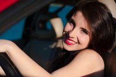 Nahaufnahme des Lächelns, herrliche jugendlich Frau im roten Lippenstift am Rad des roten Autos Lizenzfreies Stockbild