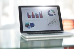 Nahaufnahme des Laptops mit Diagrammen auf Schirm auf weißem modernem Schreibtisch Lizenzfreie Stockfotos