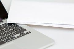 Nahaufnahme des Laptops und des Weißbuches Stockfotos