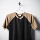 Nahaufnahme des leeren Baumwollt-shirts braun und der schwarzen Farben, die in der leeren MittelBetonmauer hängen Klares Aufklebe Stockbild