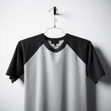 Nahaufnahme des leeren Baumwollt-shirts grau und der schwarzen Farben, die in der leeren MittelBetonmauer hängen Klares Aufkleber Stockfotografie