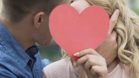 Nahaufnahme des leidenschaftlichen Kusses der liebevollen Leute, des Mannes und der Frau, die Papierherz hält stock video