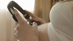 Nahaufnahme des Mädchens der schwangeren Frau mit Kopfhörern auf ihrem Bauch stock footage