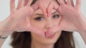 Nahaufnahme des Mädchens Herz mit den Fingern zeigend stock footage