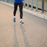 Nahaufnahme des männlichen Sports bemannt die Beine, die bei Sonnenuntergang laufen Gesunder Lebensstil und Sportkonzept stockbild