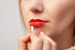 Nahaufnahme des Makes-up der Lippen eines Modells mit einem hellfarbigen Gesicht, der Make-upkünstler hält ein Wattestäbchen in s lizenzfreie stockbilder