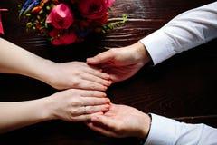 Nahaufnahme des Mann- und Frauenhändchenhaltens bei der Kreuzung von The Creek Fokus auf Händen von Paaren lizenzfreie stockfotos